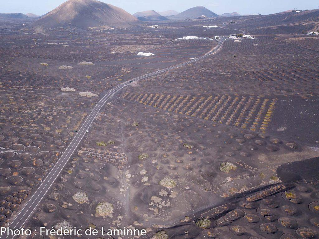 La route LZ30 traverse la zone viticole de La Géria à Lanzarote. Bodegas La Geria et Rubicon à l'arrière plan.